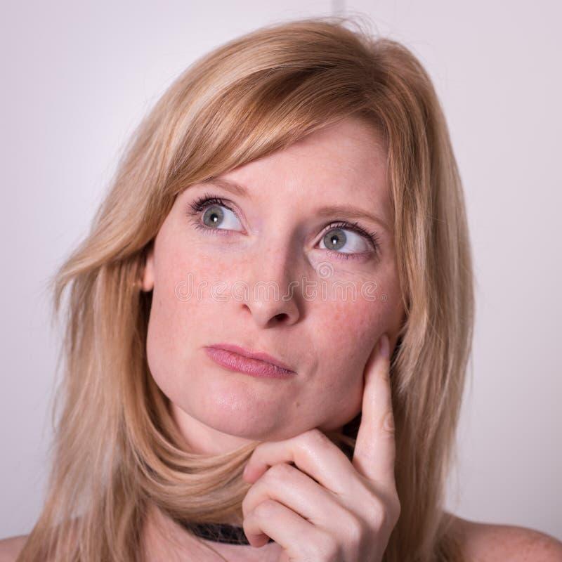Den härliga blonda kvinnan ser upp och att tänka arkivfoto