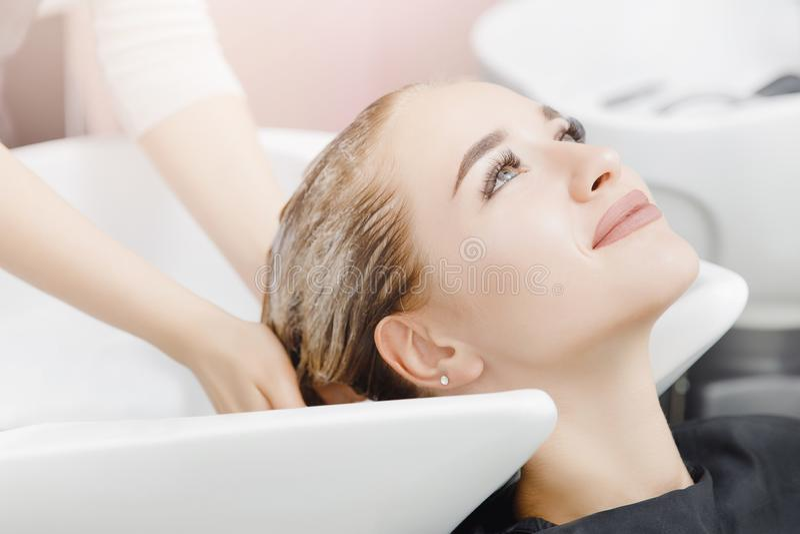 Den härliga blonda kvinnan som får hår, tvättar sig i skönhetsalong Begreppshuvudmassage arkivfoton