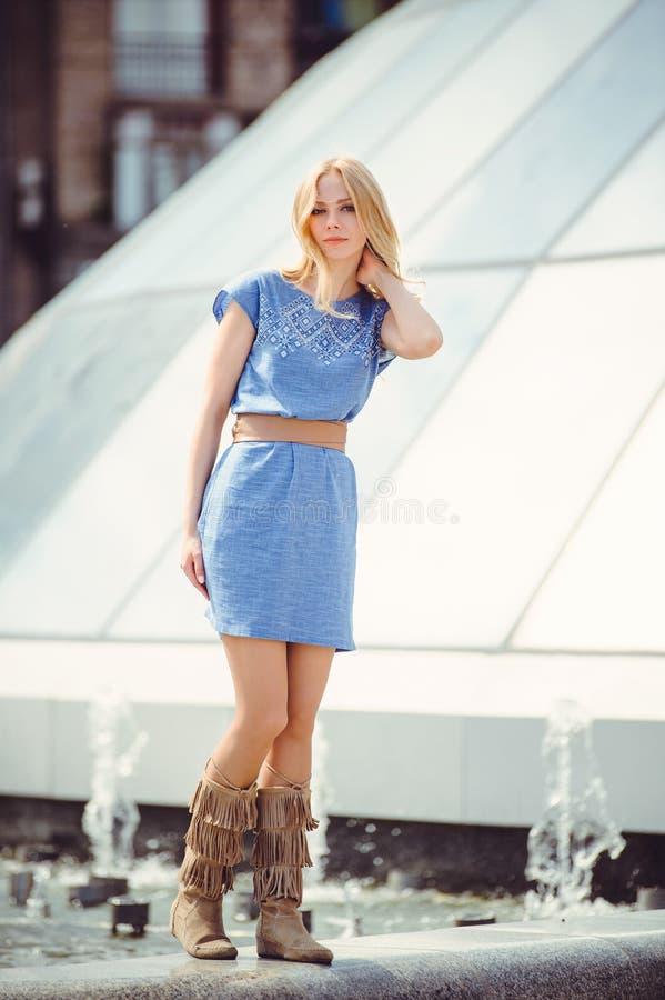 Den härliga blonda kvinnan som går i den iklädda staden en blå klänning och kängor som, är blygsamma och, skyggar, händer som try fotografering för bildbyråer