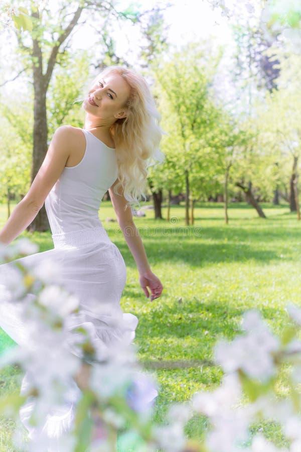 Den härliga blonda kvinnan tycker om i den blommande trädgården fotografering för bildbyråer