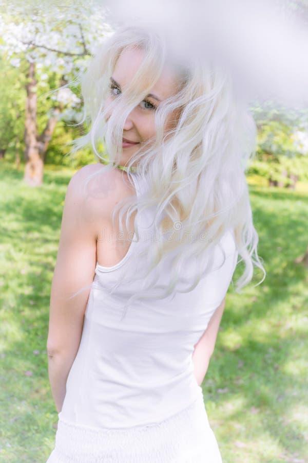 Den härliga blonda kvinnan tycker om i den blommande trädgården royaltyfria foton