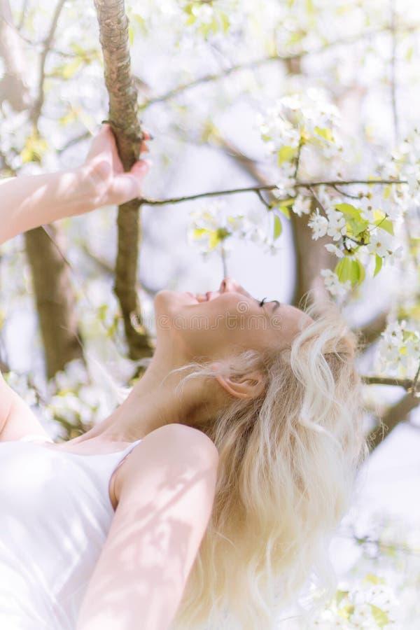 Den härliga blonda kvinnan tycker om i den blommande trädgården arkivbild
