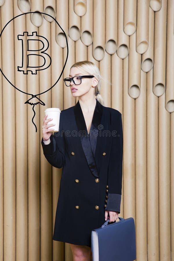 Den härliga blonda kvinnavisningen som står near bitcoin, skissar Faktiskt pengar- eller btcfruktdryckbegrepp Cryptocurrency royaltyfri fotografi