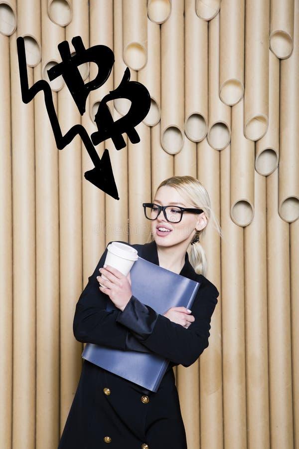 Den härliga blonda kvinnavisningen som står near bitcoin, skissar Faktiskt pengar- eller btcfruktdryckbegrepp Cryptocurrency royaltyfria foton