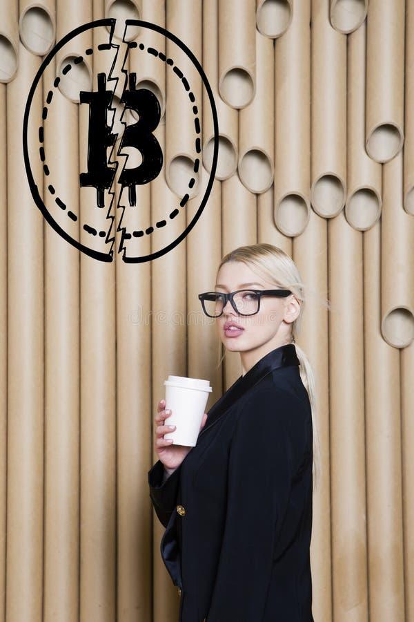 Den härliga blonda kvinnavisningen som står near bitcoin, skissar Faktiskt pengar- eller btcfruktdryckbegrepp Cryptocurrency arkivfoto
