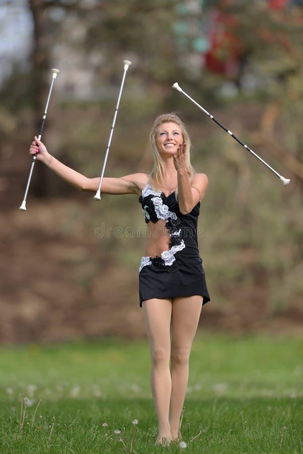 Den härliga blonda kvinnliga twirleren eller majoretten utför royaltyfria bilder
