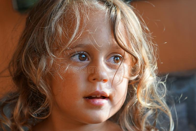 Den härliga blonda lilla flickan ser från sidan fotografering för bildbyråer