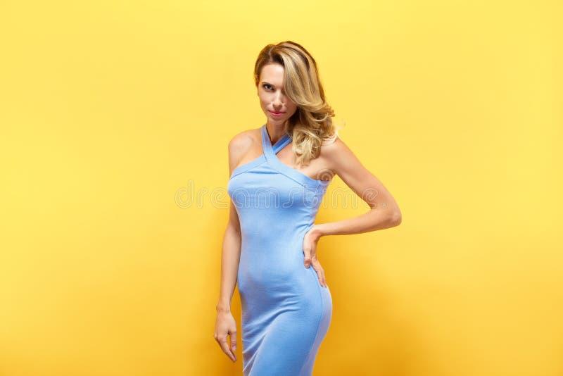 Den härliga blonda modellen i blått klär att posera på kameran fotografering för bildbyråer