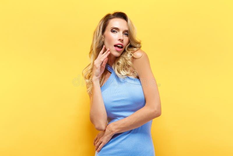 Den härliga blonda modellen i blått klär att posera på kameran arkivbilder