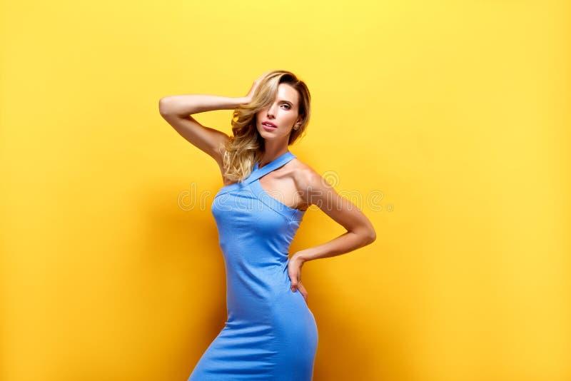 Den härliga blonda modellen i blått klär att posera på kameran royaltyfria foton