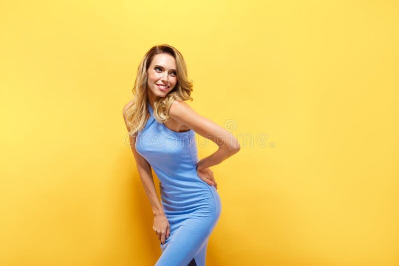 Den härliga blonda modellen i blått klär att posera på kameran royaltyfri bild