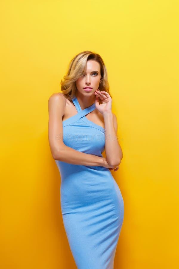 Den härliga blonda modellen i blått klär att posera på kameran royaltyfri fotografi