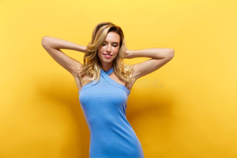 Den härliga blonda modellen i blått klär att posera på kameran royaltyfri foto