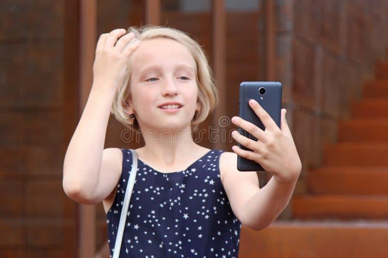 Den härliga blonda preteenflickan som använder en telefon, gör fotoet en främre kamera som tar en självstående med mobiltelefonen royaltyfri fotografi
