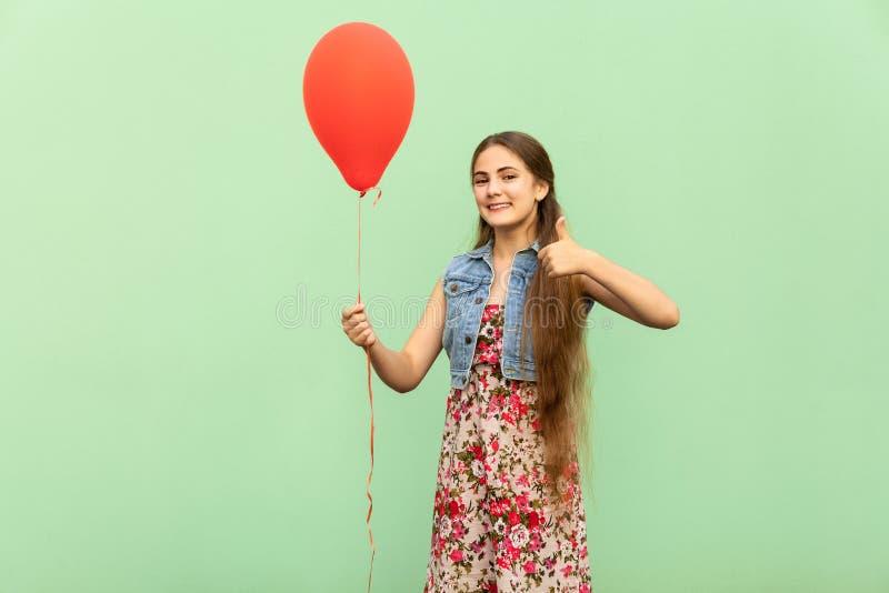 Den härliga blonda tonåringen med röda ballons, tummar up och det toothy leendet, på en grön bakgrund arkivbild