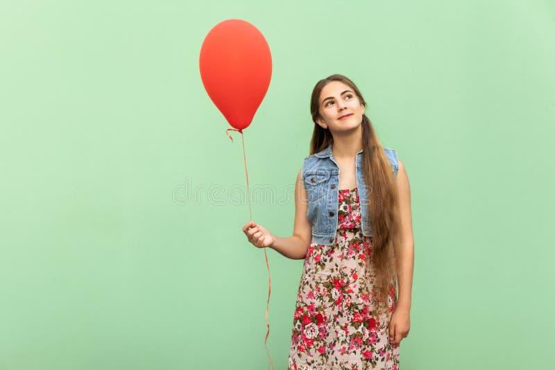 Den härliga blonda tonåringen som drömmer, med röd ballon på ett ljus - grön bakgrund fotografering för bildbyråer