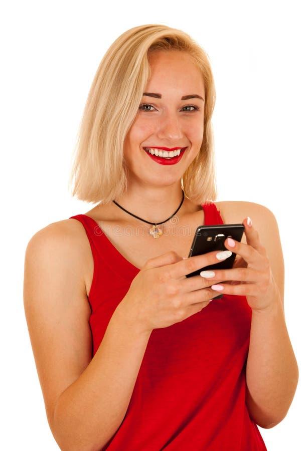 Den härliga blonda tonårs- flickan som smsar på den smarta telefonen, isolerade ov royaltyfria bilder