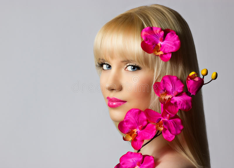 Den härliga blonda ung flicka med orchiden blommar på grå färgbackgrou royaltyfria foton