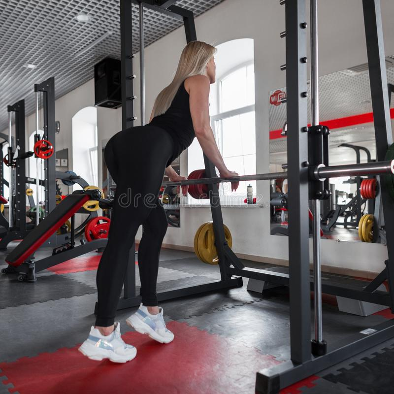 Den härliga blondinen för den unga kvinnan i sportswear med en härlig slank kropp står nära en metallsimulator i en konditionstud royaltyfria foton
