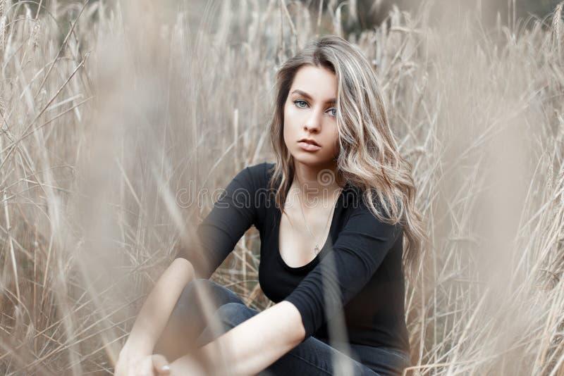 Den härliga blondinen för den unga kvinnan i stilfull jeans i en trendig svart skjorta vilar royaltyfria bilder