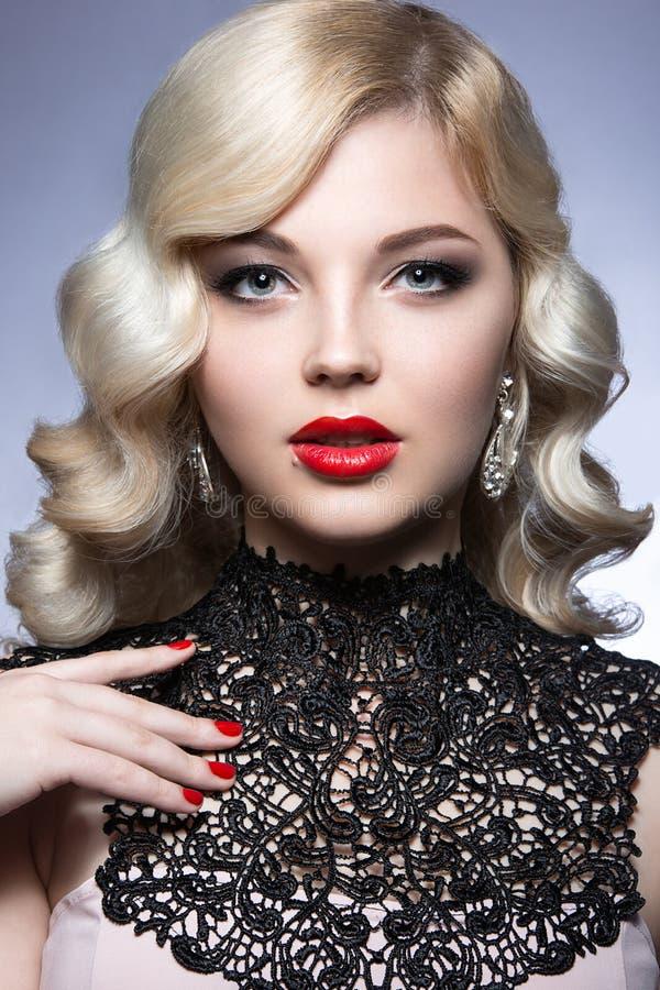 Den härliga blondinen i ett Hollywood sätt med krullning, röda kanter och snör åt klänningen Härlig le flicka royaltyfria bilder