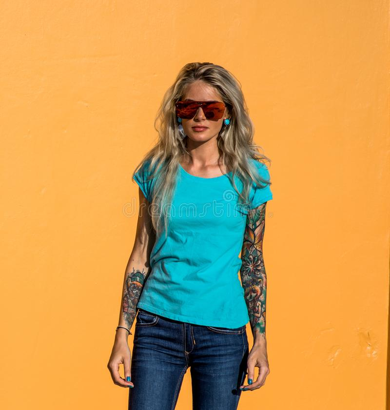 Den härliga blondinen i solglasögon ser kameran Stående på bakgrunden av den ljusa orange väggen Modern hipsterflicka arkivfoton