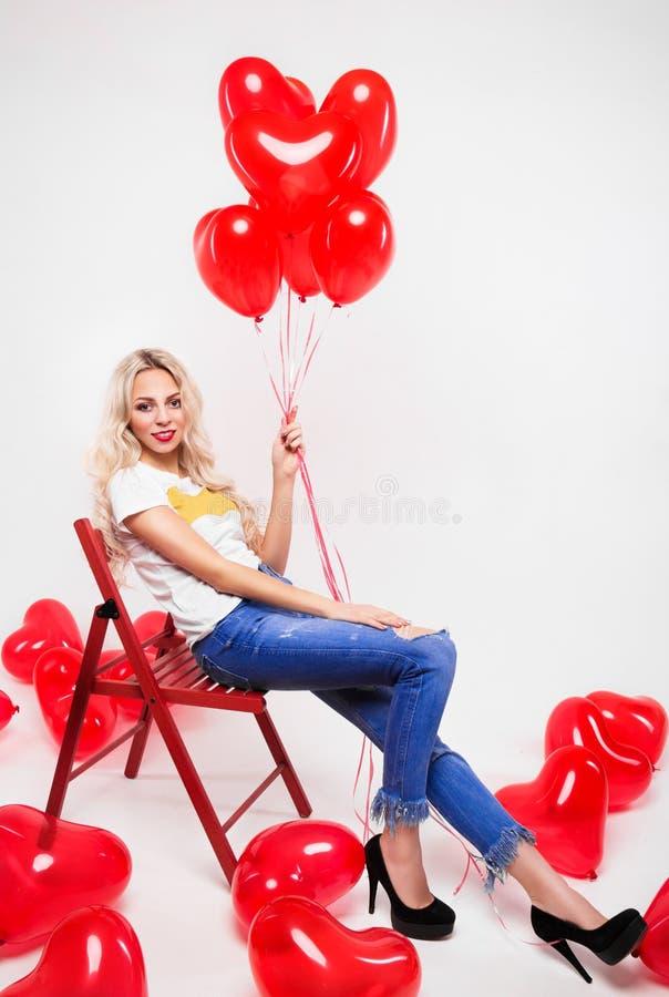 Den härliga blondinen med långa ben sitter på stol Flicka med röda bollar på en vit bakgrund valentin för dag s fotografering för bildbyråer
