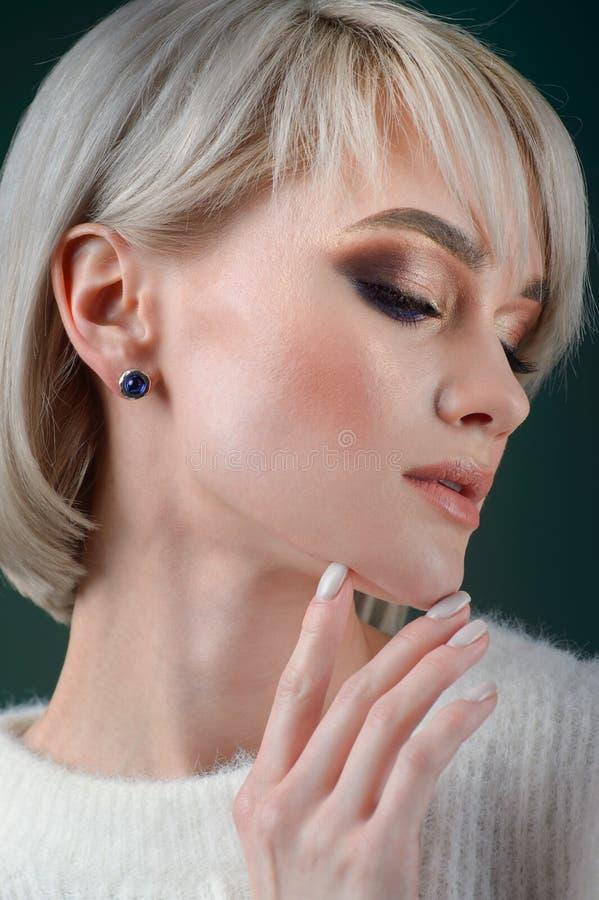Den härliga blondinen med lyxigt försilvrar smycken Kvinnan bär försilvrar smycken royaltyfri foto