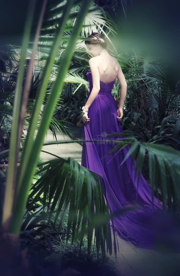 Den härliga blyga flickan i långa lilor klär royaltyfri foto
