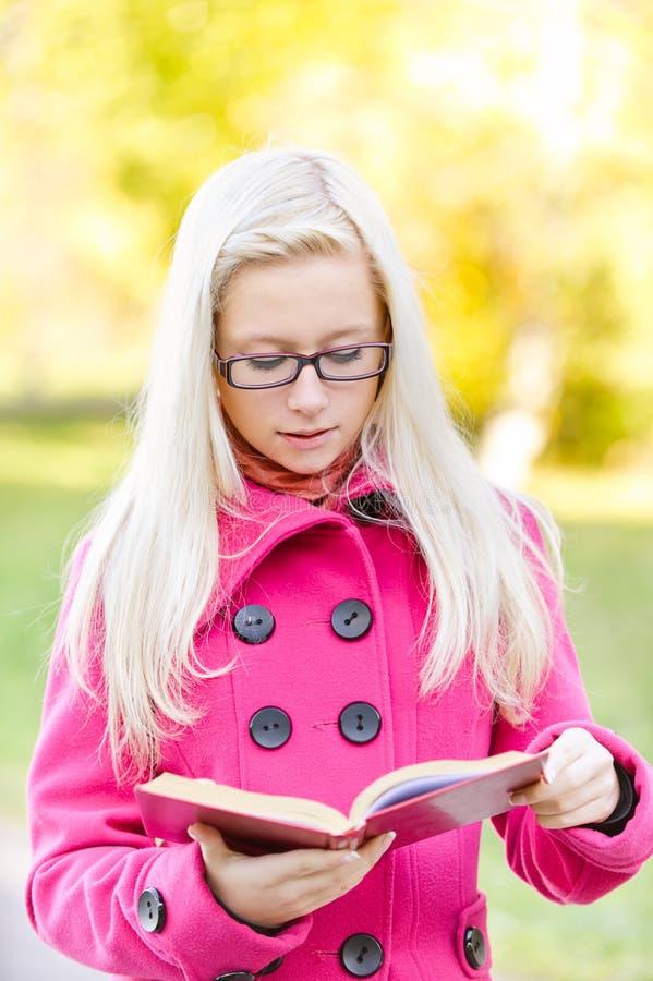 den härliga bokflickan läser red royaltyfri fotografi