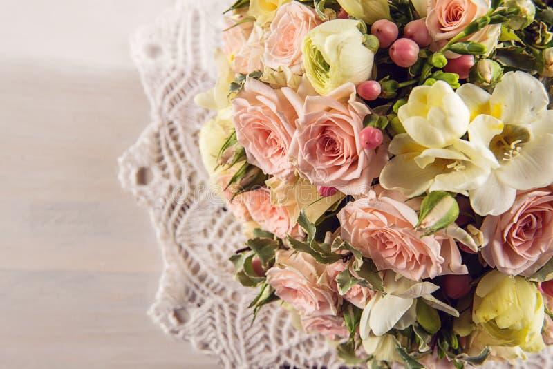 Den härliga bröllopbuketten av rosor och freesia med snör åt på vit träbakgrund, bakgrund för valentin eller bröllopdag royaltyfri foto