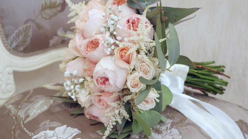 Den härliga bröllopbuketten med rosa färger blommar att ligga på stolen i rummet royaltyfri foto