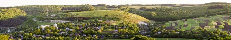 Den härliga breda flyg- sikten av den lilla byn bland gräsplanträdgårdar, lappad panorama av mörker plogade och den gräsplanfält  arkivfoton