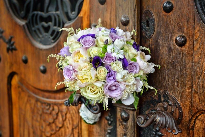 Den härliga brud- buketten av kulöra rosor ligger på den wood dörren arkivfoto