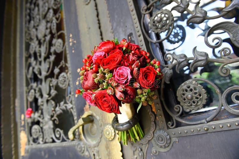 Den härliga brud- buketten ligger på dörrhandtaget royaltyfri fotografi