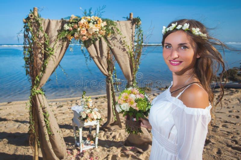 Den härliga bruden att gifta sig på stranden, Bali bröllop för brudceremoniblomma fotografering för bildbyråer