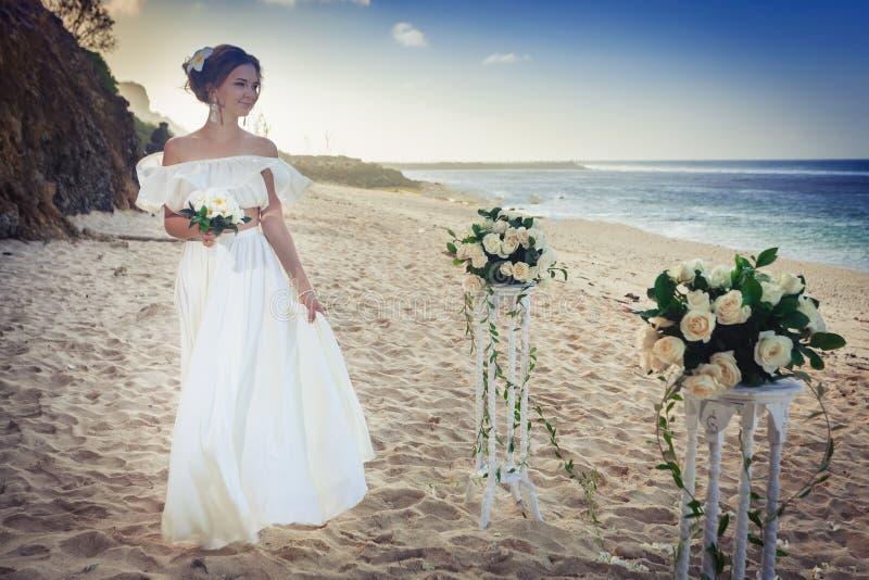 Den härliga bruden att gifta sig på stranden, Bali bröllop för brudceremoniblomma arkivbild