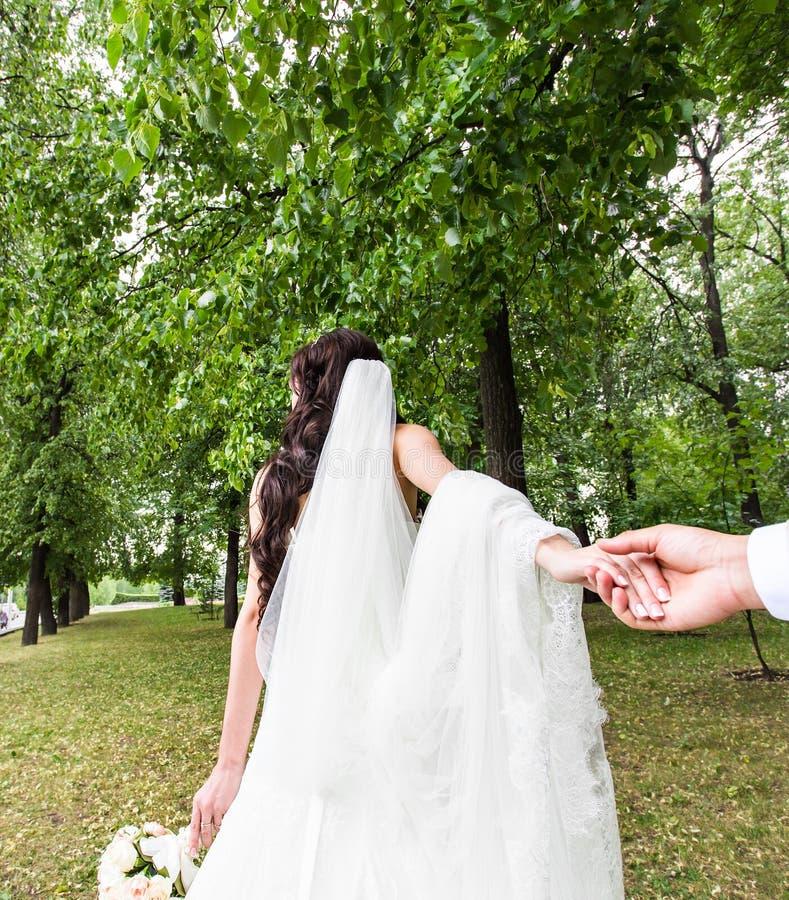 Den härliga bruden för den unga kvinnan rymmer handen av en man i utomhus Följ mig royaltyfri bild
