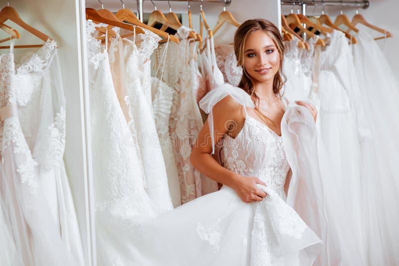 Den härliga bruden försöker på en elegant bröllopsklänning royaltyfria bilder