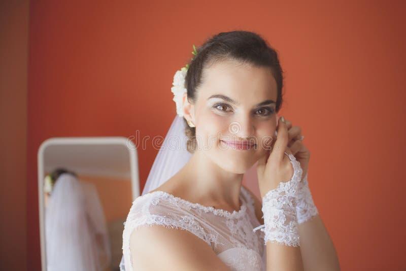 Den härliga bruden i den vita bröllopsklänningen sätter på örhänget arkivfoton