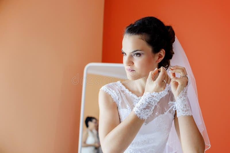 Den härliga bruden i den vita bröllopsklänningen sätter på örhänget arkivbilder