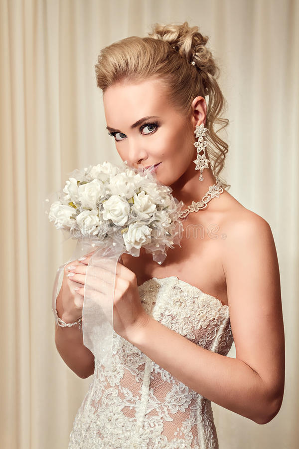 Den härliga bruden i elegant vit snör åt bröllopsklänningen arkivfoto