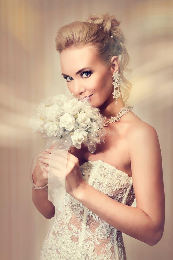 Den härliga bruden i elegant vit snör åt bröllopsklänningen royaltyfria bilder