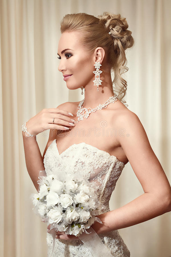Den härliga bruden i elegant vit snör åt bröllopsklänningen arkivfoton