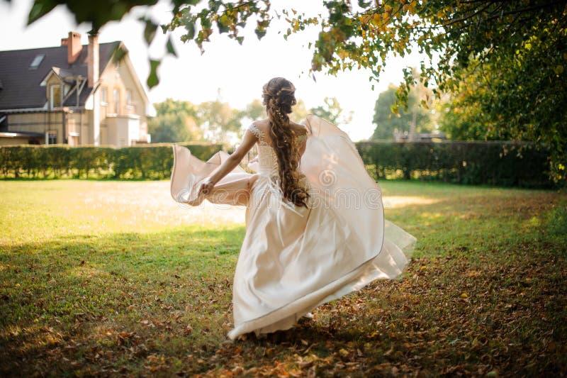 Den härliga bruden i en vit bröllopsklänning som kör i hösten, parkerar royaltyfria foton