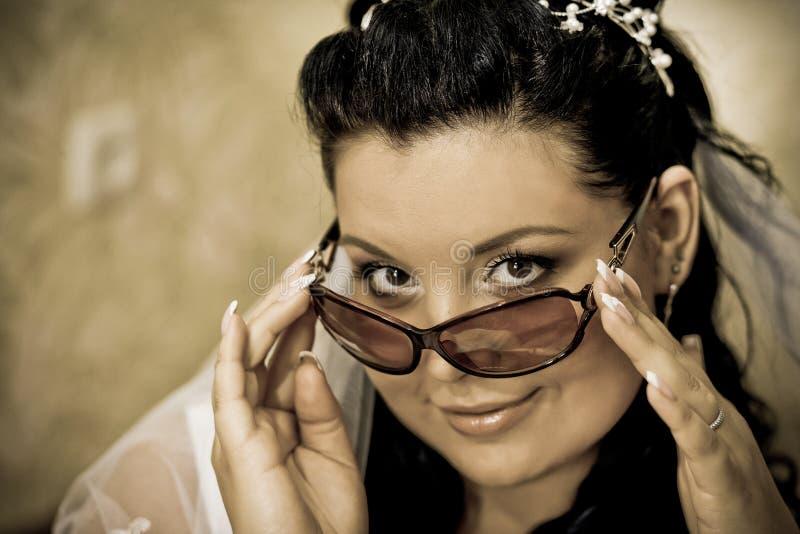 Den härliga bruden i exponeringsglas och vit skyler oemotståndlig blick för blickar fotografering för bildbyråer