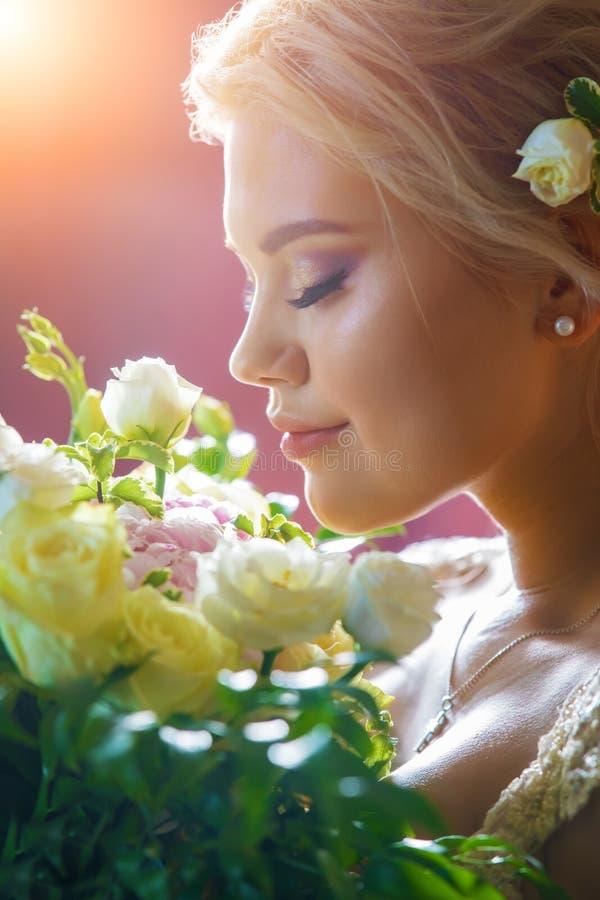 Den härliga bruden inhalerar aromen av blommorna royaltyfria bilder