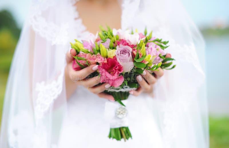 Den härliga bruden rymmer en färgrik bukett för bröllop Skönhet av kulöra blommor Closeupgrupp av florets arkivfoton