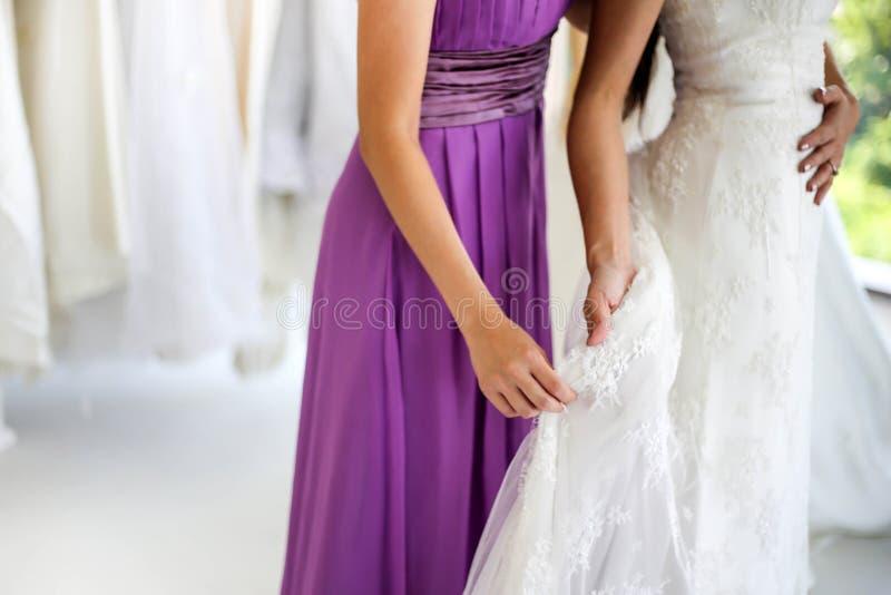 Den härliga bruden som får klädd av hennes bästa vän i hennes gifta sig dag och väljer en bröllopsklänning i, shoppar, och shoppa arkivfoton