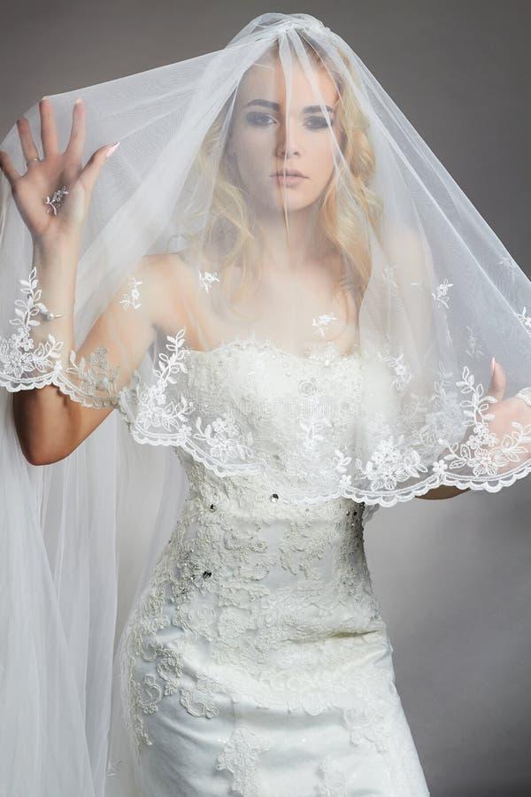 Den härliga brudkvinnan i bröllopsklänning och skyler royaltyfria bilder